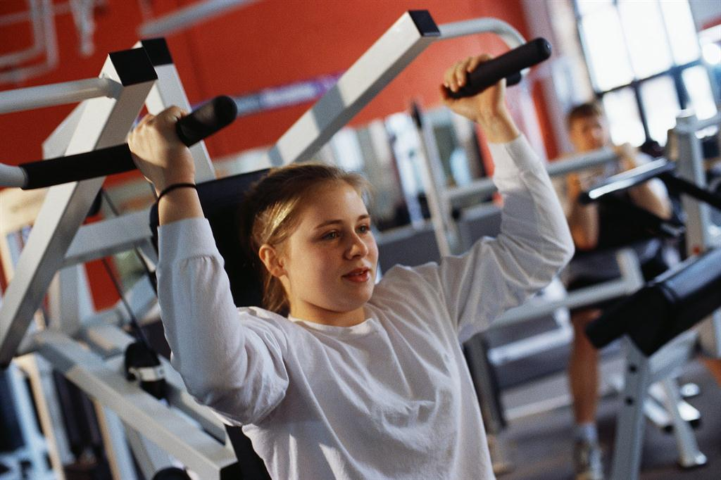 teen girl lifting weights to help with back pain